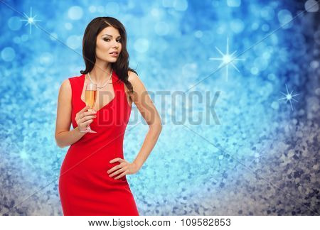 people, holidays, christmas and celebration concept - beautiful sexy woman in red dress with champagne glass over blue glitter and lights background