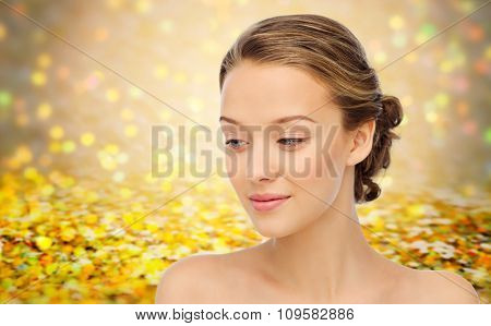 beauty, people and health concept - smiling young woman face and shoulders over golden holidays lights or yellow glitter background