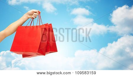 people, sale, consumerism, advertisement and commerce concept - close up of hand holding red blank shopping bags over blue sky and clouds background