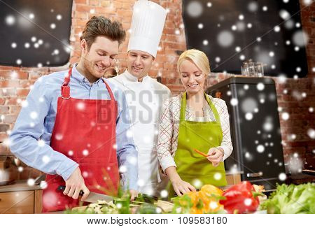 cooking class, culinary, food and people concept - happy couple and male chef cook cooking in kitchen over snow effect
