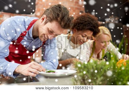 cooking class, friendship, food and people concept - happy women cooking and decorating plates with dishes in kitchen over snow effect