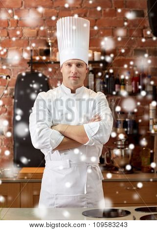 cooking and people concept - happy male chef cook with crossed hands in restaurant kitchen over snow effect