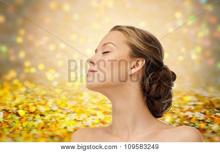 beauty, people and health concept - young woman face with closed eyes and shoulders side view over golden holidays lights or yellow glitter background