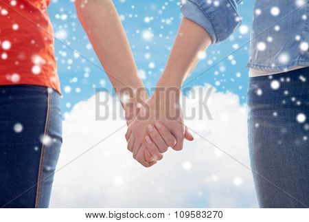 people, homosexuality, same-sex marriage, gay and love concept - close up of happy lesbian couple holding hands over blue sky and cloud background over snow effect