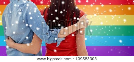 people, homosexuality, same-sex marriage, gay and love concept - close up of happy lesbian couple hugging over rainbow flag background over snow effect