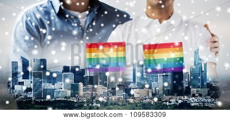 people, homosexuality, same-sex marriage, gay and love concept - close up of happy male gay couple hugging and holding rainbow flags over city background and snow effect