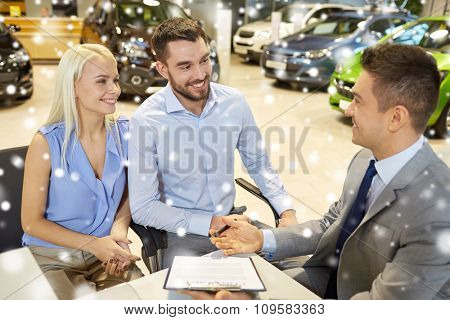 auto business, sale and people concept - happy couple with dealer buying car in auto show or salon over snow effect