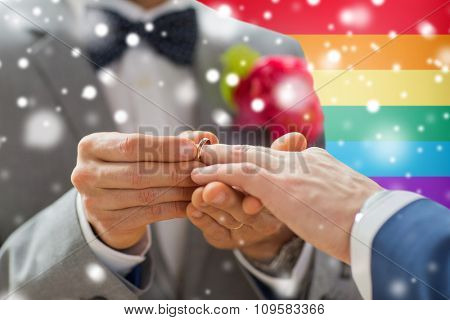 people, homosexuality, same-sex marriage and love concept - close up of happy male gay couple hands putting wedding ring on over rainbow flag background and snow effect