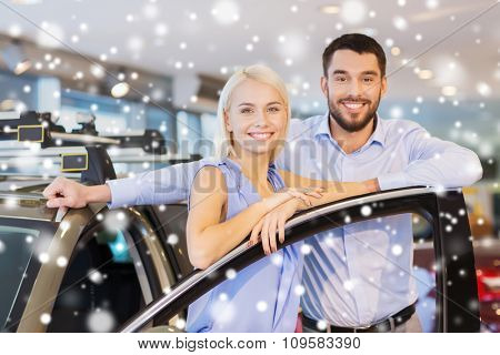 auto business, car sale, consumerism and people concept - happy couple with car in auto show or salon over snow effect
