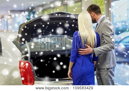 auto business, car sale and people concept - happy couple choosing car in auto show or salon over snow effect from back