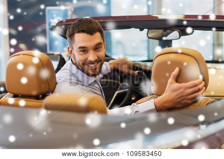 auto business, car sale, consumerism and people concept - happy man sitting in car at auto show or salon over snow effect