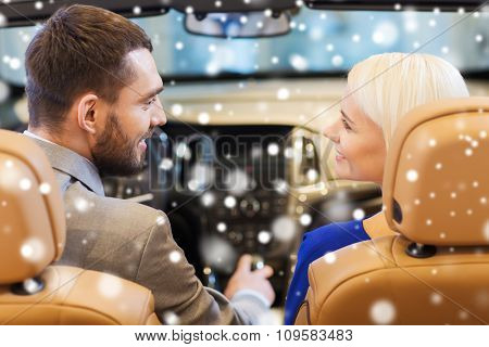 auto business, car sale, consumerism and people concept - happy couple sitting in car at auto show or salon over snow effect