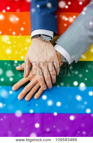 people, homosexuality, same-sex marriage, gay and love concept - close up of happy male gay couple hands over rainbow flag over snow effect