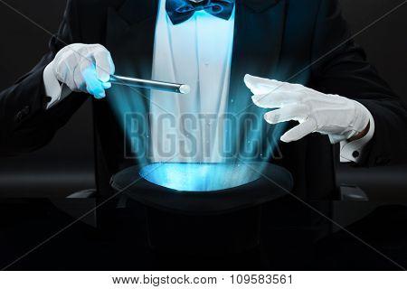 Magician Holding Magic Wand Over Illuminated Hat