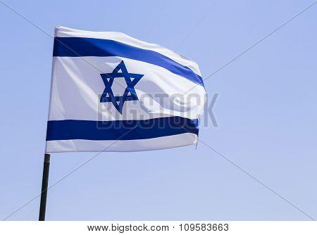 Israeli flag against blue skies