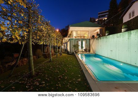Beautiful modern house by night, swimming pool
