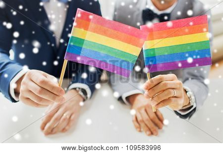 people, homosexuality, same-sex marriage and love concept - close up of happy male gay couple in suits and bow-ties with wedding rings holding rainbow flags over snow effect