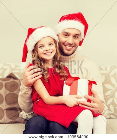 family, christmas, x-mas, happiness and people concept - smiling father and daughter in santa helper hats holding gift box