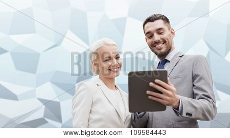 business, partnership, technology and people concept - smiling businessman and businesswoman with tablet pc computer over gray blue graphic low poly background