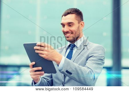 business, education, technology and people concept - smiling businessman working with tablet pc computer on city street