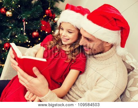 family, christmas, x-mas, happiness and people concept - smiling father and daughter in santa helper hats reading book