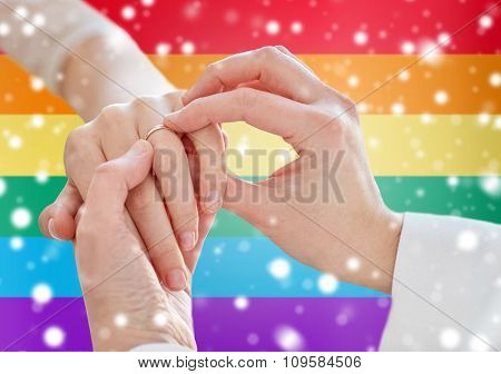 people, homosexuality, same-sex marriage and love concept - close up of happy lesbian couple hands putting on wedding ring over rainbow flag background over snow effect