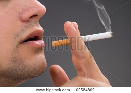 Man Smoking Against Gray Background