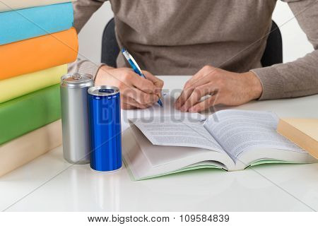 Male Student Writing In Book At Table