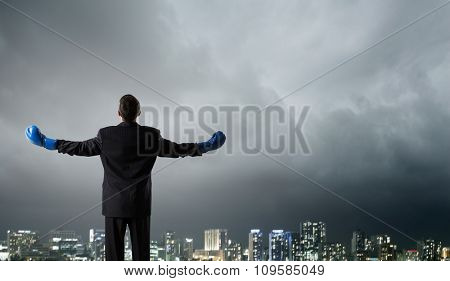 Back view of businessman in blue boxing gloves on city background