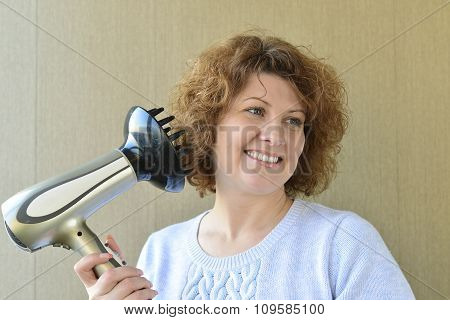 Woman doing curls with  hairdryer and diffuser