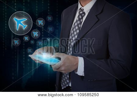 Businessman hand touch screen airplane sign icons on a tablet.