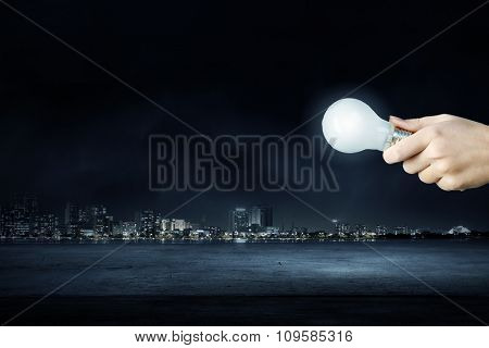 Hand holding glass glowing lightbulb in darkness