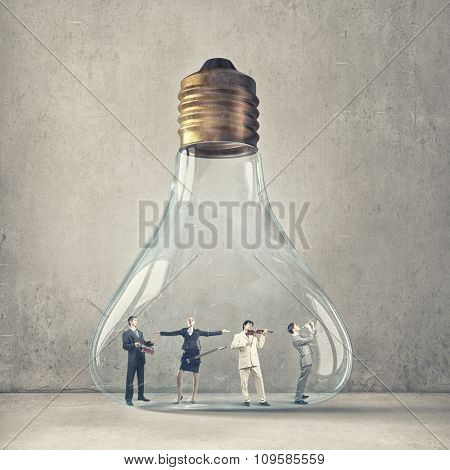 Business people in glass light bulb playing different music instruments