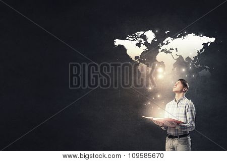 Young businessman with opened book in hands and world map on background