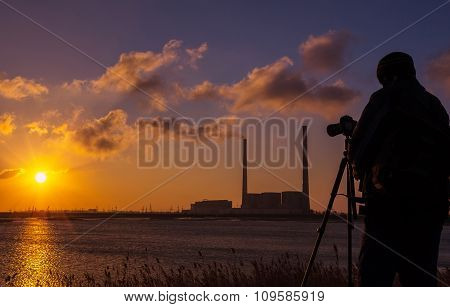 Photographer At Sunrise On The Coast, On A Background Of Giant Pipes