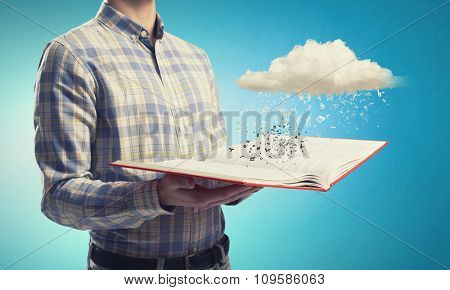 Young man with book in hands and cloud concept