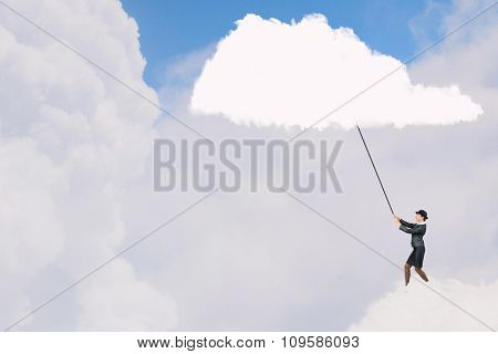 Young businesswoman in bowler hat pulling white cloud with rope