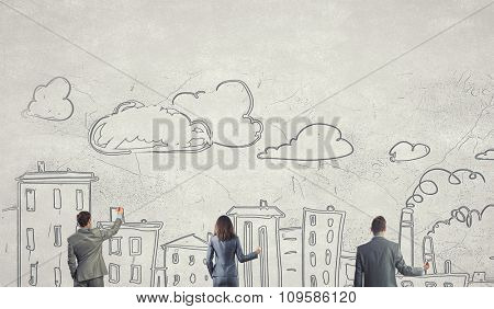 Business team standing with back drawing business concepts on wall