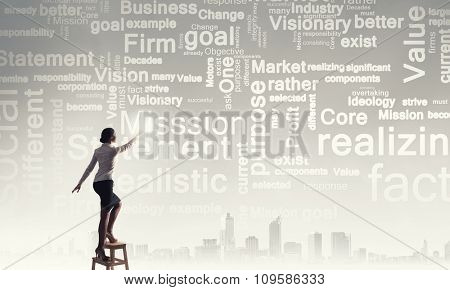 Businesswoman standing on chair and reaching leadership concepts