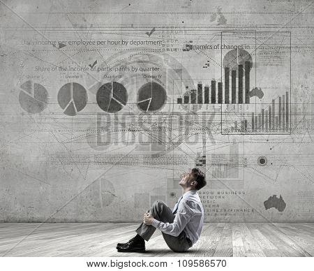 Young businessman sitting on floor in room and infographs on wall