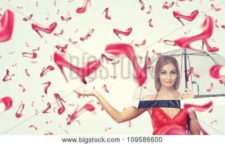 Beautiful young woman with umbrella and falling shoes