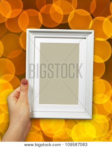 Wooden frame in beautiful woman hands on the background christmas bokeh
