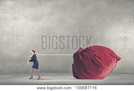 Woman in Santa hat pulling huge red gifts bag