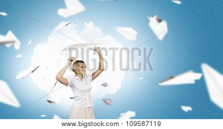 Young carefree woman with paper plane in hands
