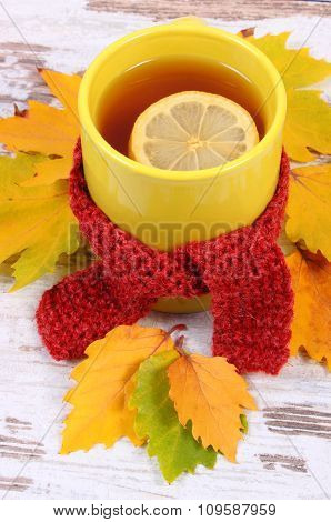 Cup Of Hot Tea With Lemon Wrapped Woolen Scarf And Autumnal Leaves, Warming Beverage For Flu