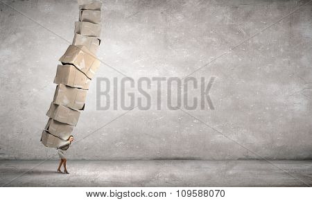 Businesswoman carrying big stack of carton boxes on her back