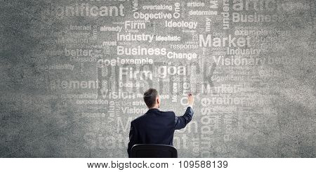 Rear view of businessman writing leadership conceptual words on wall