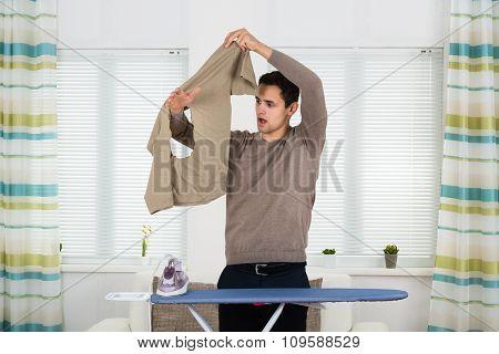 Shocked Man Looking At Iron Burnt Tshirt