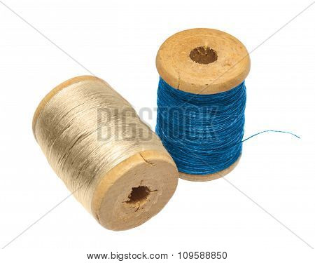 Two Wooden Spool Threads From The Blue And The Beige Threads On A White Backdrop