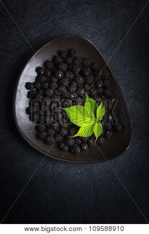 Fresh Blackberry And Green Leaf On Black Plate